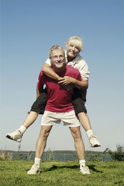 mature man giving piggy back ride to woman